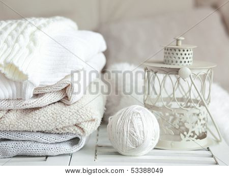 Stack of cozy knitted sweaters and lantern on a table