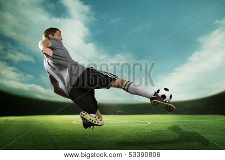 Soccer player kicking the soccer ball in mid air