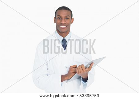Portrait of a smiling male doctor with clipboard against white background