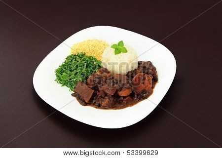 Brazilian Feijoada dish on a brown background.