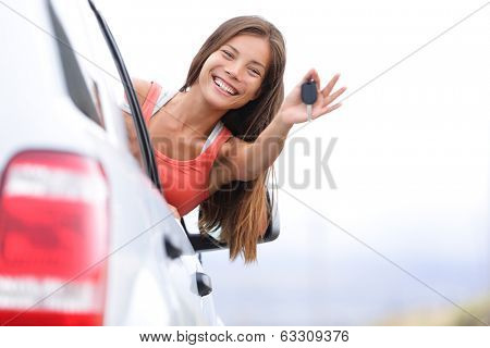 Car driver woman happy showing car keys out window. New car, rental or driving licence concept with young female model on road trip. Mixed race Asian Caucasian girl in her 20s.