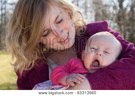 Baby Is Yawning In Mothers Arms