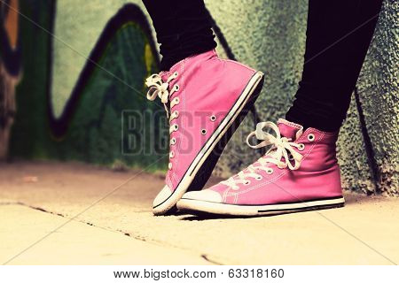 Close up of pink sneakers worn by a teenager. Grunge graffiti wall, concepts of teen rebel, problems of the youth, drugs, alcohol. poster