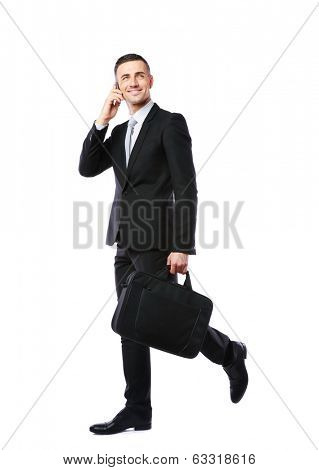 Businessman walking and talking on the phone over white background