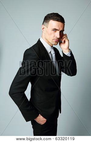 Confident businessman talking on his mobile phone on gray background