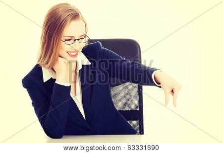 Attractive business woman sitting bt the table and advertising small thing between finger. Isolated on white.
