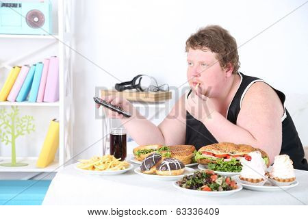 Fat man has a big lunch and watching TV, on home interior background