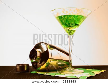 Apple Martini on a colorful napkin and shaker laying on its side.