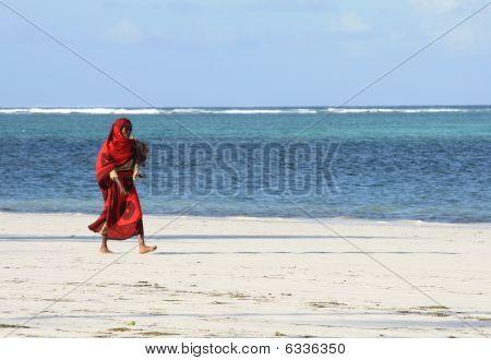 Zanzibar Woman In Red On Sandy Beach