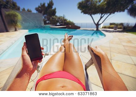Woman In Bikini Reclining On Chair With Phone
