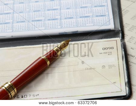 A pile of bills, checkbook, pen on the table.