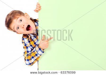 Cute surprised boy peeking out from behind a white board. Copy space. Isolated over white.