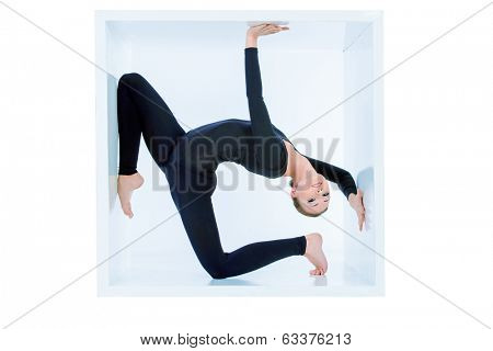 Modern ballet dancer posing with a cube at studio. Plastic body concept. Isolated over white.