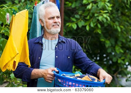 Cheerful Senior Man With Laundry Basket Outdoor