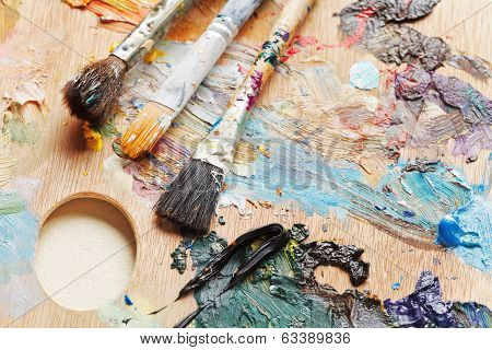 Three Used Paint Brushes On Artistic Pallette
