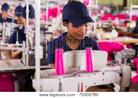 african clothing factory worker sewing with colleagues on background