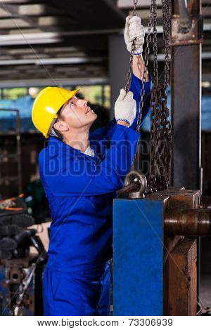 industrial worker in uniform pulling chains