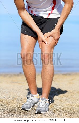 Muscle injury. Man runner with sprain thigh muscles. Athlete running in sports shorts clutching his thigh muscles after pulling or straining them while jogging on the beach.