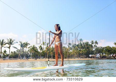 Hawaii beach lifestyle woman paddleboarding in bikini.on SUP. Beautiful multiethnic woman surfing on stand up paddleboard on Big Island, Hawaii. Multiracial Asian Caucasian girl.