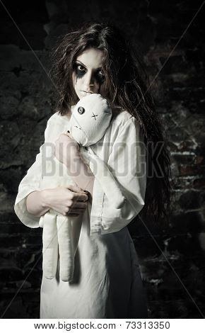 Horror Shot: Sad Strange Girl With Moppet Doll In Hands
