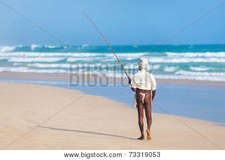 UNAWATUNA, SRI LANKA - MARCH 9, 2014: Elderly stilt fisherman at Unawatuna Beach. Most real stilt fishermen have been long gone. Today it's mainly young boys posing as stilt fishermen for tourists.