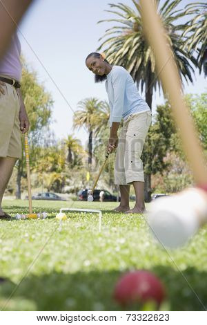 Mixed Race woman playing croquet
