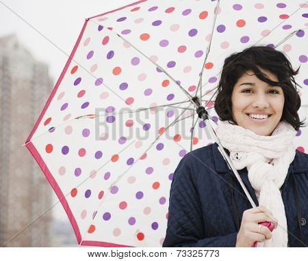 Hispanic woman walking in city with umbrella