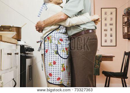 Senior couple hugging in kitchen
