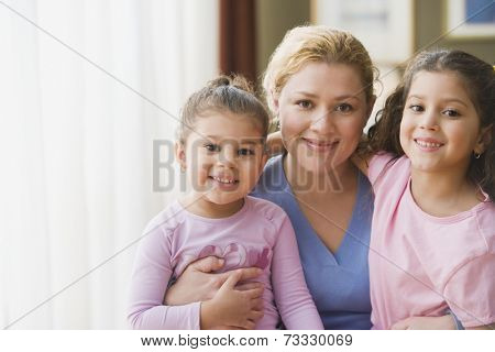 Hispanic mother hugging daughters indoors