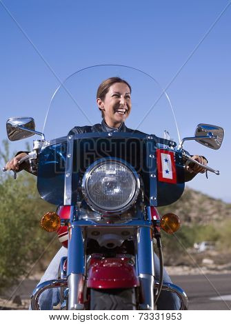 Hispanic woman sitting on motorcycle