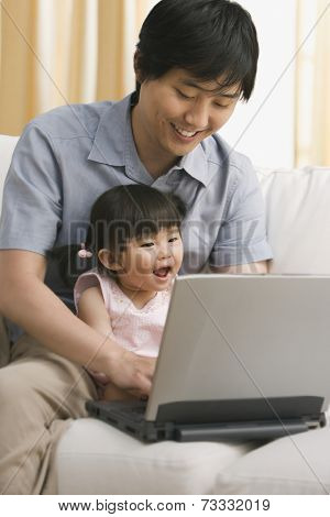 Asian father and baby daughter looking at laptop