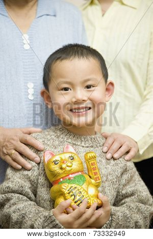 Chinese boy holding beckoning cat