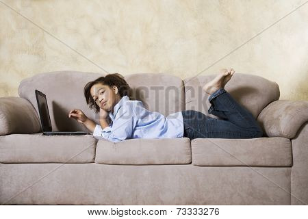 African girl with laptop on sofa