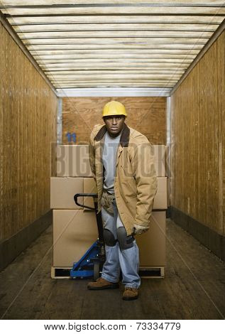 African warehouse worker pulling pallet in truck
