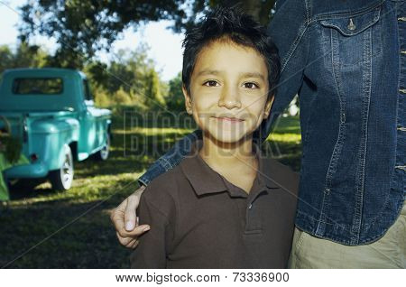 Hispanic boy with truck in background