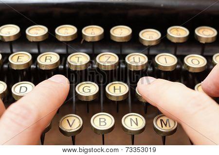 Close Up Of Man Typing With Old Typewriter