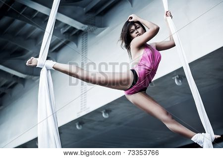 Young woman gymnast. On industrial background.