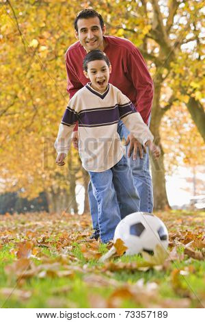 Hispanic father and son playing with soccer ball