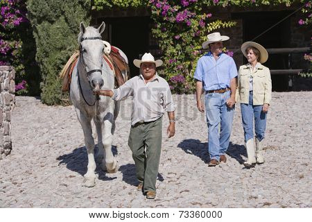 Hispanic man leading horse next to couple