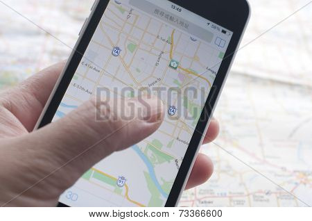 People checking smartphone with GPS navigator on map