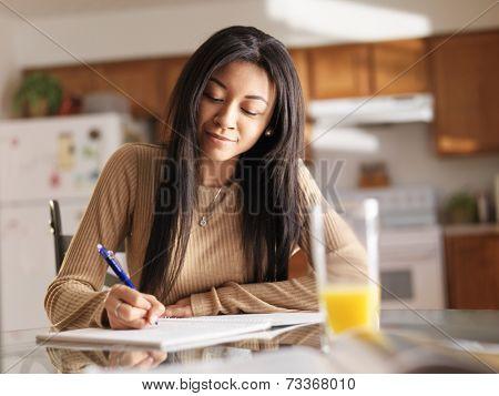 african teenager girl doing homework in kitchen before school