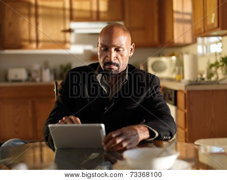 african man with tablet in early morning inside kitchen