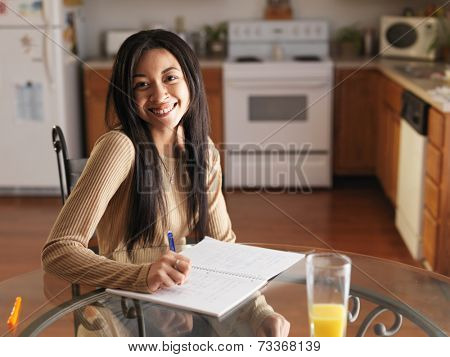 african teen girl posing with homework on kitchen table