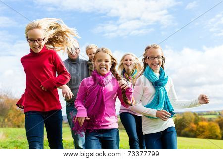 Family running through park in fall or autumn