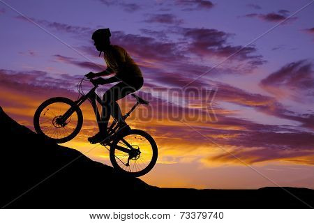 Man Riding A Bike Up A Hill Silhouette In The Sunset
