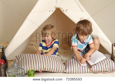 Children playing at home with a teepee tent