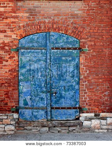 Weathered Old Door In Brick Wall