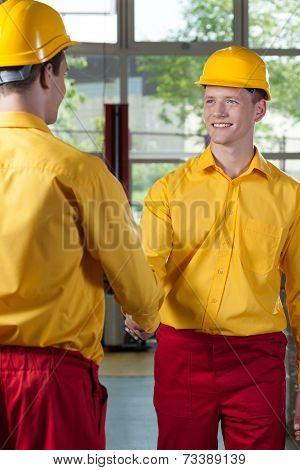 Workers Handshake In A Factory