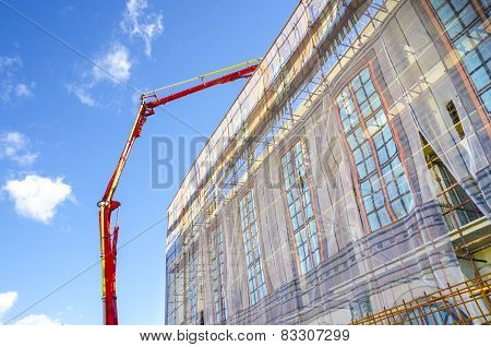 Industrial crane casting concrete on building top