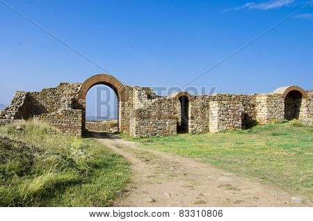 Ruins of an ancient town and path through arced gate